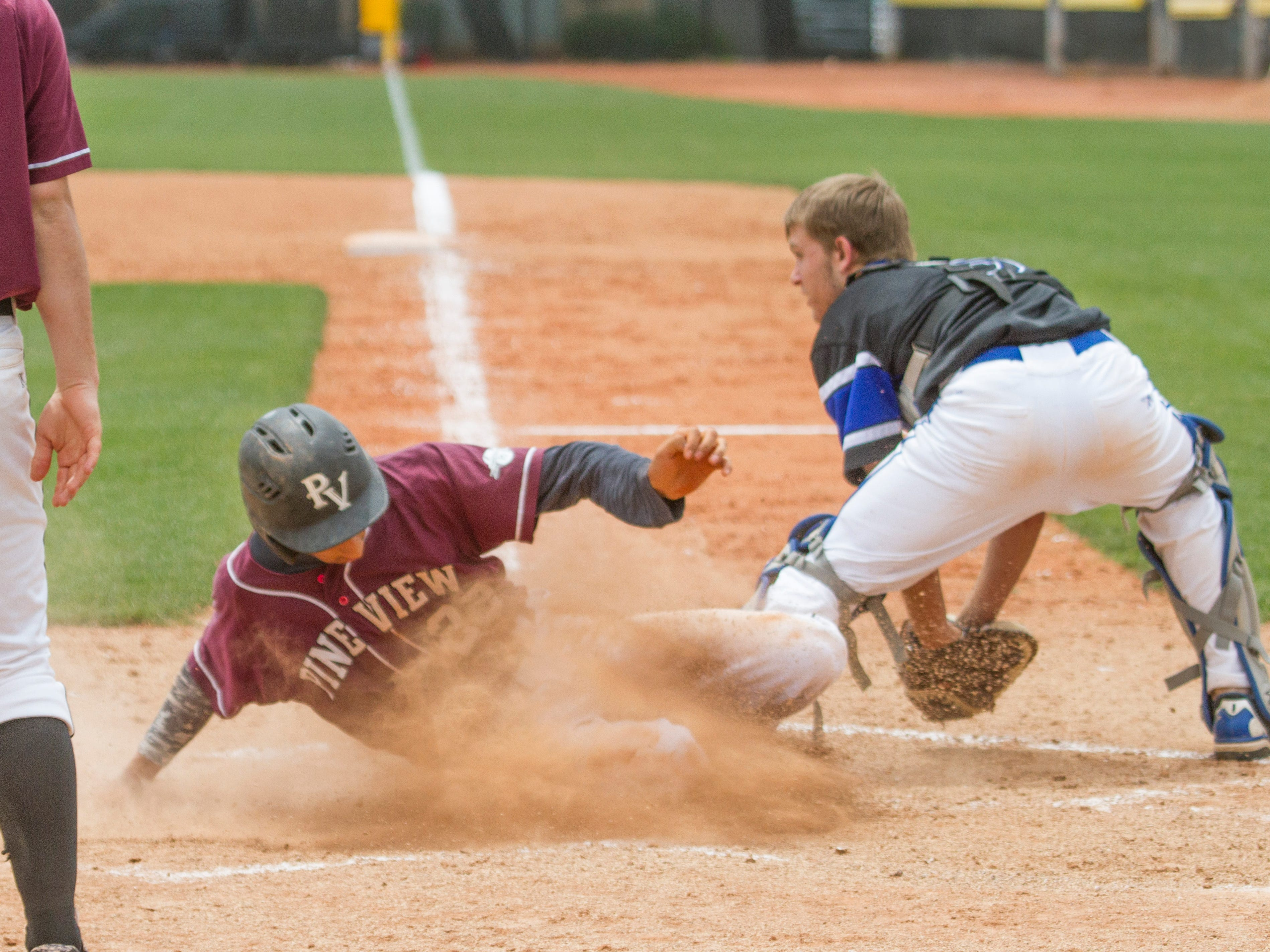 A Pine View runner slides at the plate as the Carbon catcher takes the throw Thursday.