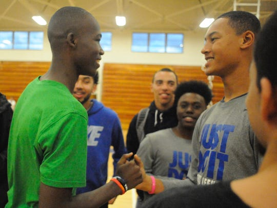 Darius George, left, is congratulated by Lee teammate Jarvis Vaughn Wednesday after George signed his national letter of intent to attend Marshall University.