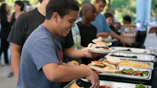 Kelvin Davilla, 13, of Rochester, serves himself a burger at Frontier Field in Rochester on July 31, 2015.