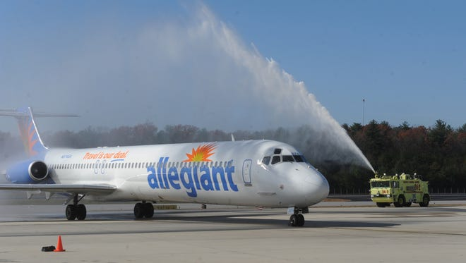A 2012 Allegiant flight is greeted by a celebratory water arch at Asheville Regional Airport. Two sisters said they were kicked off an Allegiant Air flight from Orlando, Florida, to Asheville after authorities deemed them a threat, and it cost them the chance to see their dying father.