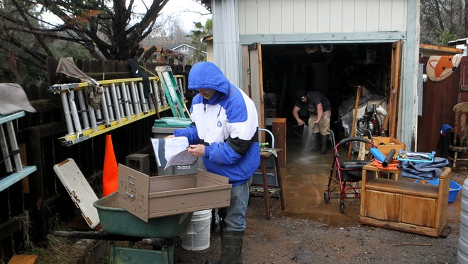 George Martikke, left, goes through paperwork while his nephew Brian Sudeta helps clean up after water flooded Martikke's home in Shasta Lake.