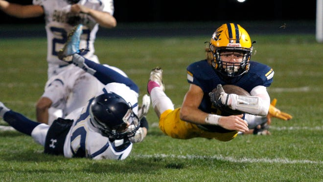 Ithaca's Seth Davis, right, dives for yardage against Shepherd's Cole Fitzpatrick Friday, Oct. 21, 2016, in Ithaca, Mich. Ithaca won 31-24.