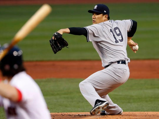 Tanaka delivers against the Boston Red Sox during the first inning at Fenway Park.