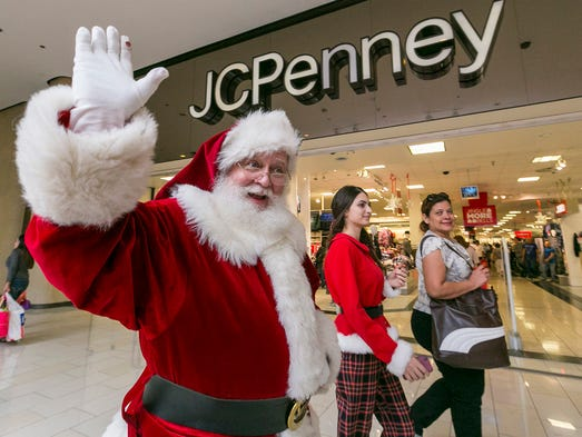 A man dressed as Santa Claus greets shoppers outside
