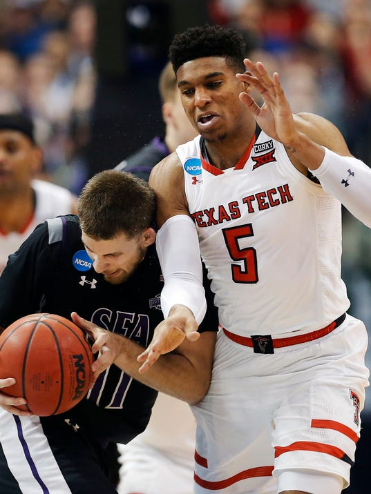 Stephen F. Austin guard Ivan Canete (11) battles Texas Tech guard Justin Gray (5) for space during the first half of a first-round game at the NCAA college basketball tournament in Dallas, Thursday, March 15, 2018. (AP Photo/Brandon Wade)