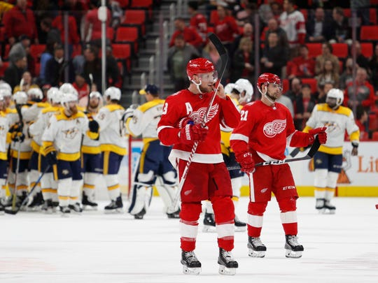 Red Wings left wing Justin Abdelkader (8) and left wing Tomas Tatar (21) skate off the ice after the Wings' 3-2 loss on Tuesday, Feb. 20, 2018, at Little Caesars Arena.