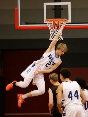 Nicolet's Jack Brahm (2) hangs on the rim after a dunk against Plymouth, Thursday, March 8, 2018, in Sheboygan, Wis.