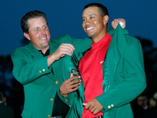 Tiger Woods gets the green jacket from Phil Mickelson