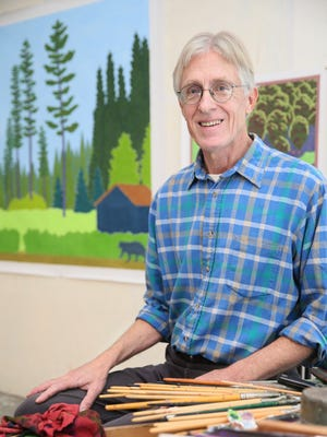 "Charles Munch of rural Lone Rock in his studio. Behind Munch is his painting titled ""Bear Country""."