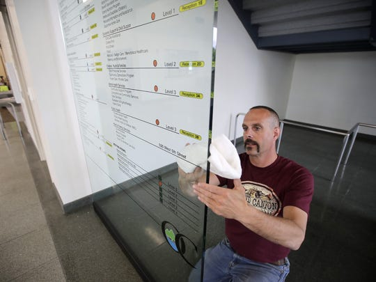 John Slaby, with Creative Sign, cleans the Outagamie County Government Center's directory in preparation for the Monday opening.
