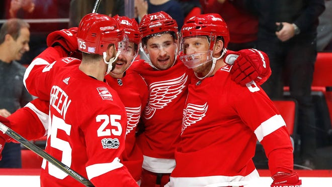 Red Wings center Dylan Larkin, third from left, celebrates a goal against the Avalanche with Mike Green (25), Xavier Ouellet (61) and Justiin Abdelkader in the first period on Sunday, Nov. 19, 2017, at Little Caesars Arena. The goal, originally credited to Larkin, was later awarded to Abdelkader.