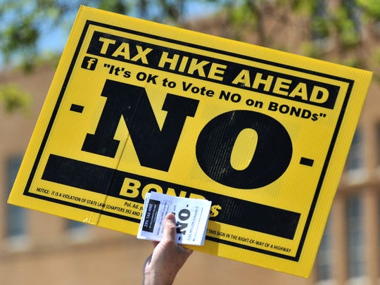 Signs are held in protest of a possible tax increase if the proposed bonds are passed by Wichita Falls voters.