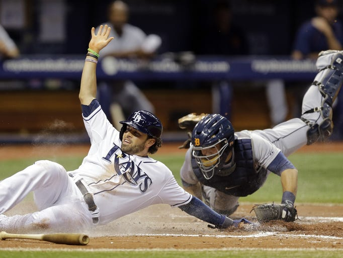 Tampa Bay Rays' David DeJesus, left, slides around