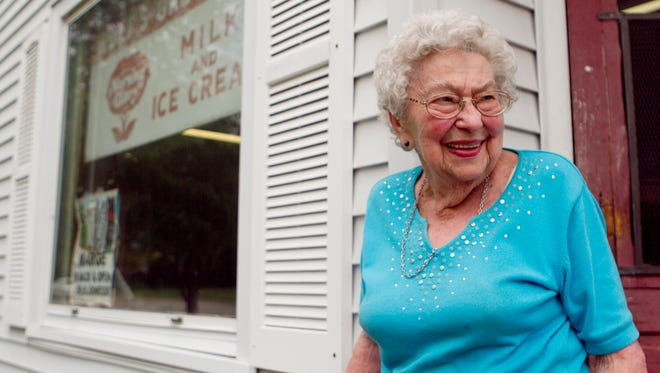 Marge Wolf stands in front of Wolf's Grocery Store in Marshfield in 2013.
