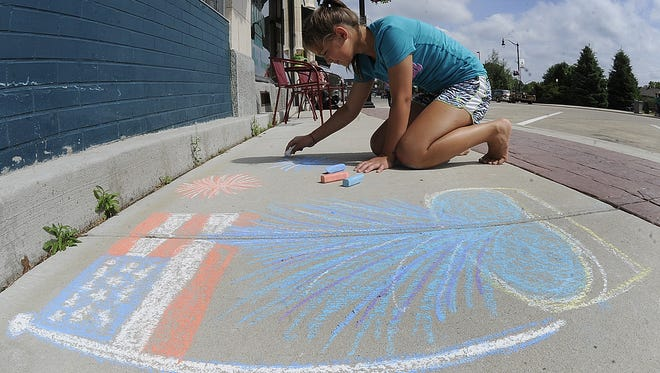 Jasmine Pleet draws artwork on the West Grand Avenue sidewalk during Chalk It Up, 2014