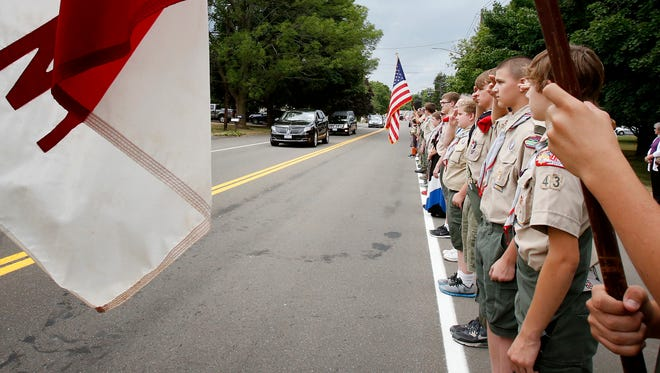 Pine City Boy Scout Troop 43 stands at attention along Broad Street in Horseheads as the hearse carrying Jim and Conner Hamilton drives to Maple Grove Cemetery on Saturday. The Hamiltons were killed in a personal watercraft crash on July 2.