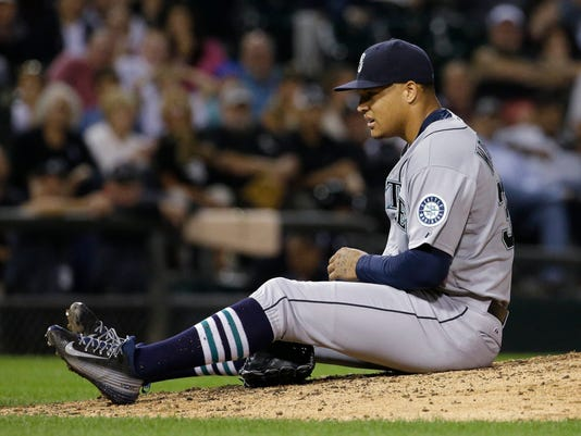 Seattle Mariners starter Taijuan Walker falls to the ground after throwing a pitch during the seventh inning of a baseball game against the Chicago White Sox, Friday, Aug. 28, 2015, in Chicago. (AP Photo/Nam Y. Huh)