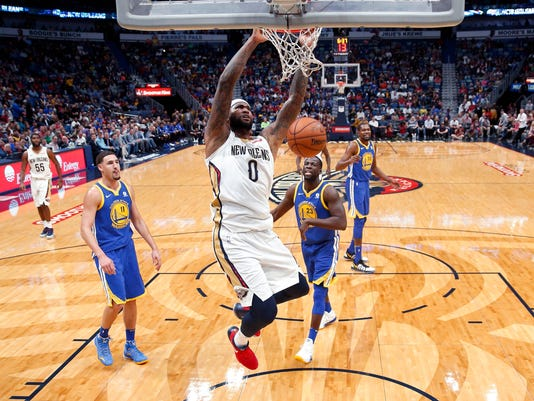 New Orleans Pelicans center DeMarcus Cousins (0) slam dunks in front of Golden State Warriors forward Draymond Green (23) and guard Klay Thompson (11) in the first half of an NBA basketball game in New Orleans, Monday, Dec. 4, 2017. (AP Photo/Gerald Herbert)