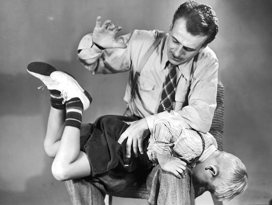 Father spanking son (5-7) on lap (B&W)