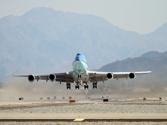 The wheels of Air Force One lift off the runway at