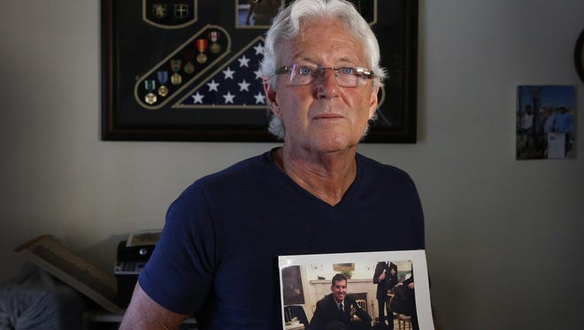 """William Owens holds a photo of his youngest son, Navy SEAL William """"Ryan"""" Owens, in Lauderdale by the Sea, Fla."""