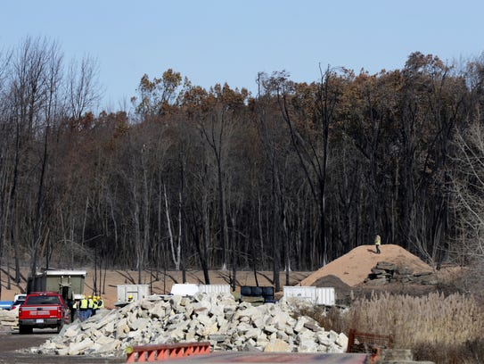Emergency personnel work at the site of a ruptured