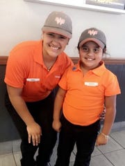Nadia Garza (left) poses with Krysta Galindo in her Whataburger employee outfit. She wanted to be just like Garza for career day at school.