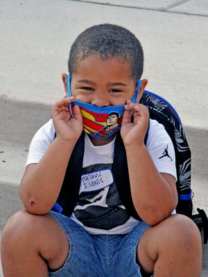 Donning a Superman face mask, Carter Davis, a kindergartener at Melrose Elementary School, sits on the steps outside the front doors Monday. His mother, Kayla Woofter, said she originally planned on having her son learn remotely this fall, but after trying it for a few months at the end of the last school year, it didn't seem like the right fit.