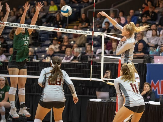 Farmington Hills Mercy's Logan Beyer (7) drills one at the Lake Orion blockers during MHSAA Volleyball semifinals at Kellogg Arena in Battle Creek.