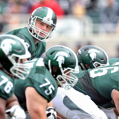 Michigan State Spartans quarterback Connor Cook  looks down the offensive line prior to the snap of the ball during the 1st quarter of a game at Spartan Stadium.
