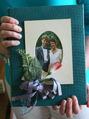 Joleen Tichelaar holds her wedding album. She and her husband Jay were high school sweethearts in Rochester, Minn., and would have celebrated their 29th anniversary on June 24. He was killed by flying debris on I-94 in Jefferson County on May 22, 2017.