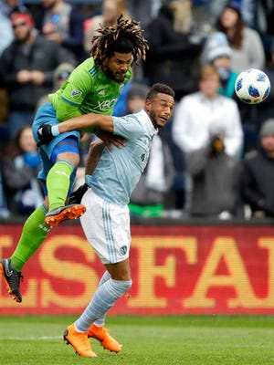 Seattle Sounders defender Roman Torres, left, heads the ball over Sporting Kansas City forward Khiry Shelton during the first half of an MLS soccer match in Kansas City, Kan. Sunday.