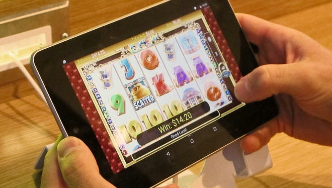 An employee at Resorts Casino Hotel tries a touchscreen tablet device the day before the opening of the casino's internet gambling lounge in Atlantic City, N.J.