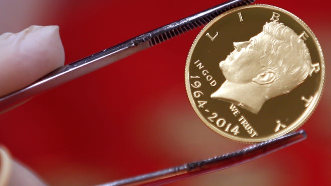 A newly-stamped gold coin of President John F. Kennedy is examined at the U.S. Mint at West Point on Tuesday. Kennedy is getting a new look on the new coin that is being made by the mint to mark the 50 years since the slain president debuted on a half-dollar.
