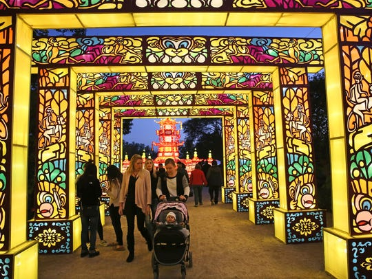People walk under a series of illuminated arches at