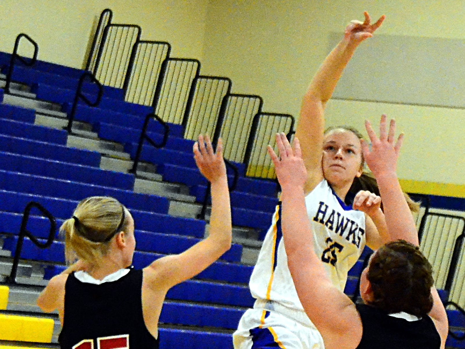 Merrol Hyde Magnet freshman Gabrielle Steiner releases a shot over Aaron Academy junior Erin Fuqua (15) and sophomore Abbie Conner (33) during first-quarter action.