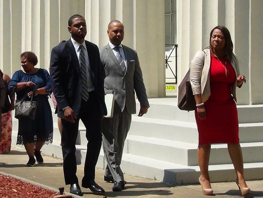 From right attorneys Tiffani Collins, Carlos Moore and Jason Downs walk ahead the family of Crystalline Barnes at news conference May 15, 2018, at city hall in Jackson, Miss.