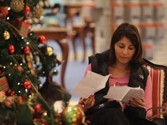 Janet Paris of Mendon checks over her Christmas shopping list of 23 people while she and family members that came with her, sit and wait for gifts to be wrapped at Von Maur located in the Eastview Mall.