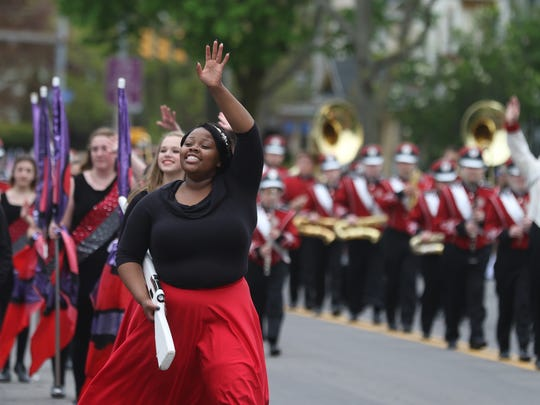 Myranda Powell and others in the Hilton Crimson Cadets Marching Band wave to the crowd before starting their performance during the Lilac Festival Parade.