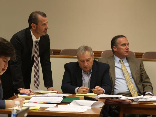 Alexander Rideout writes notes while his brother's attorney, Matthew Parrinello objects.  Paul Tucci, also writes notes while seated beside his attorney, Michael Schiano.