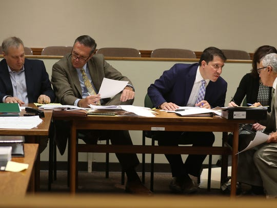 Paul Tucci confers with his attorney, Michael Schiano, while Laura Rideout's attorneys David Pilato and Michael DiPrima talk quietly to each other.