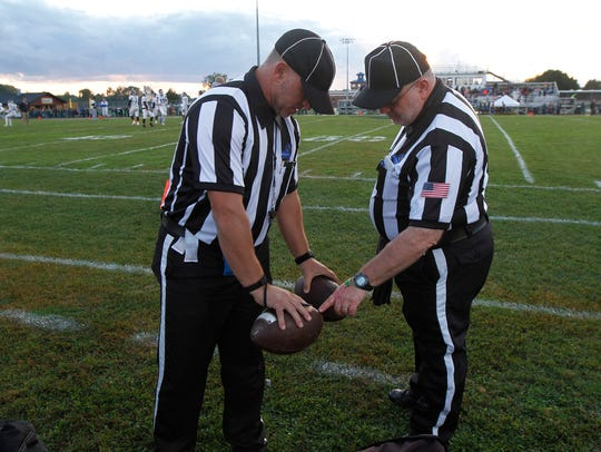 Referees Bob Bates And Father Paul Bonacci Look Over