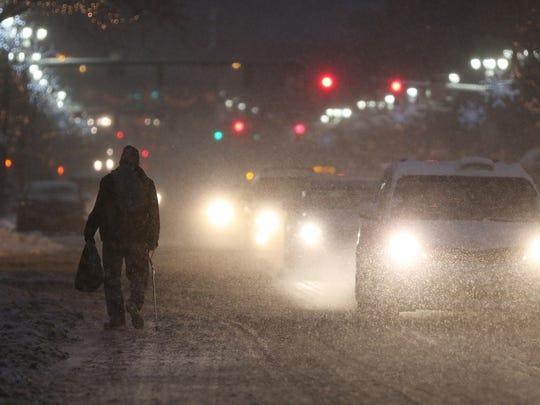 A pedestrian heads east on Main Street during a snowstorm.