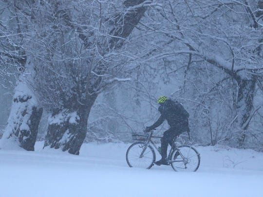 A bicyclist makes his way through Genesee Valley Park on a snowy trail.