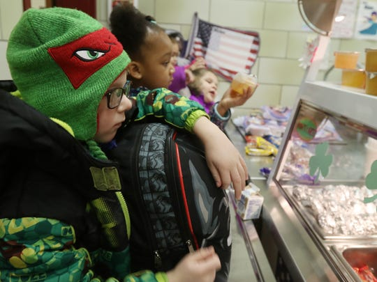 Students at Neil Armstrong Elementary School in Gates can get breakfast and take it back to their class. Breakfast is offered to any student, those who qualify for free meals and those who pay. Jayden DeGrande, a first-grader, looks at what's offered for breakfast in the school cafeteria, before grabbing cereal. Behind him in line is Jaraiya Jenkins, a kindergartner.