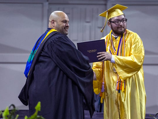 "Ezequiel ""Zeke"" Cuestas (right) takes a photograph with Tony Elizondo, president of the CCISD Board of Trustees, as he graduates from Miller High School on Friday, June, 1 2018 at the American Bank Center. He was told he wouldn't be able to walk the stage to graduate due to Leukemia, but went to physical therapy twice a week to be strong enough to walk the stage. He is currently in remission."