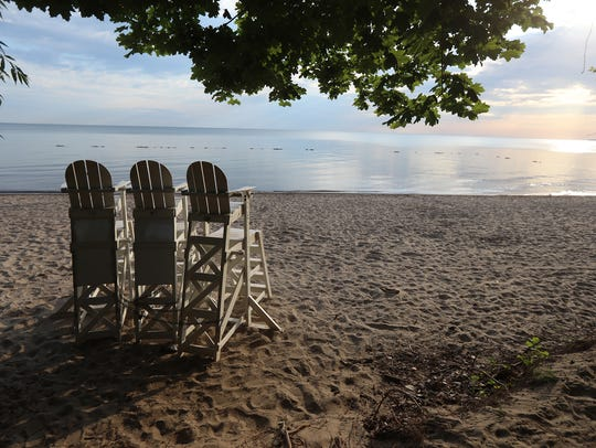 Three empty chairs alongside a still Lake Ontario at Durand-Eastman Beach in Rochester.