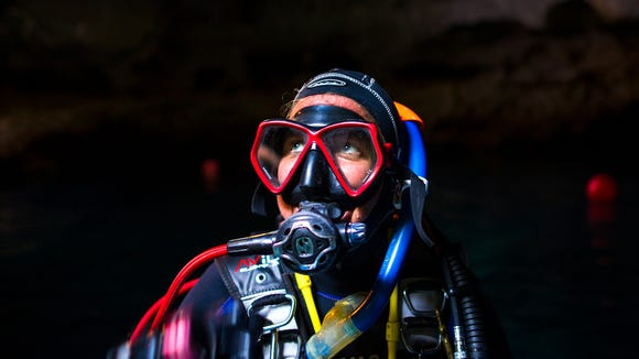 Gabrielle Gabrielli, a scuba instructor from Tallahassee, looks up to the roof of the den before her dive on Monday, August 21, 2017 at the Devil's Den Spring near Williston, Florida. Gabrielli has been to the den many times to scuba.