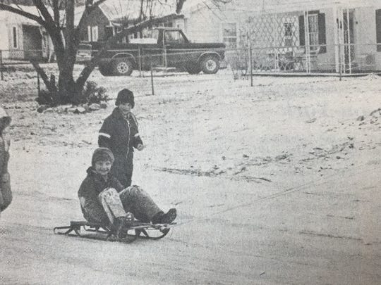 In December 1985, school was canceled for the second Friday in a row due to an inch of snow. Pictured enjoying the day off are Jason Kirby, 10, right, and Carlie Beth Beaven, 5, left. In the center are Craig Bolds, 10, and Troy Willett, 8.