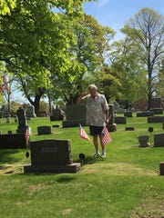 Roger R. Dufek salutes a fallen veteran as he places